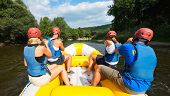 picture of down jacket  - A group of friends in an inflatable raft moving down a river - JPG