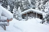 stock photo of loneliness  - Small wooden blockhouse in winter under the white snow in the snowy forest of pine trees winter landscape - JPG
