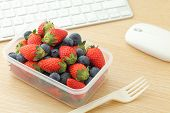 stock photo of lunch box  - Berry mix lunch box in working desk - JPG