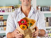 Midsection of male customer showing bellpeppers in paper bag at supermarket