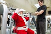 stock photo of crazy hat  - Santa Claus  exercise with personal trainer in the gym - JPG