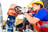 In utility or factory ewo technicians or engineers working on a valve on building technical equipmen