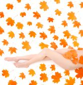 foto of woman legs  - Long beautiful legs of nudity woman covering by maple leafs over white - JPG
