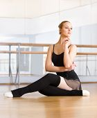 stock photo of ballet barre  - Ballet dancer does exercises sitting on the floor in the classroom with barre and mirrors - JPG