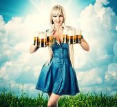 stock photo of bavaria  - young sexy oktoberfest woman wearing a dirndl holding six beer mugs - JPG