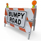 stock photo of overcoming obstacles  - The words Bumpy Road on a barrier or blockade as a warning sign that trouble - JPG