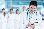 stock photo of hospital  - Happy doctor using tablet computer at the hospital - JPG