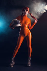 stock photo of fetish clothes  - Sexy girl in orange latex catsuit holding helmet - JPG