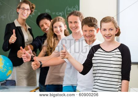 School class teacher and students stand in front of a blackboard with math work in a classroom during lesson
