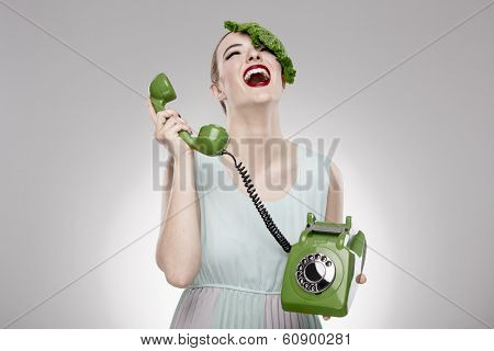 Portrait of a woman illustrating a vegan concept with a cabbage on the head and making a ecological green call