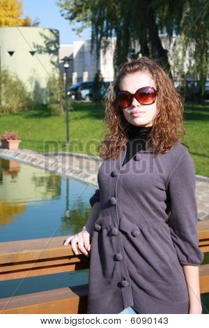 Brown-haired Woman  Costs On The Bridge In Sun Glasses