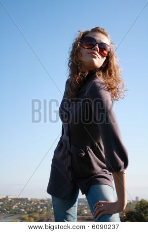 Girl In Sun Glasses Poses Against The Blue Sky