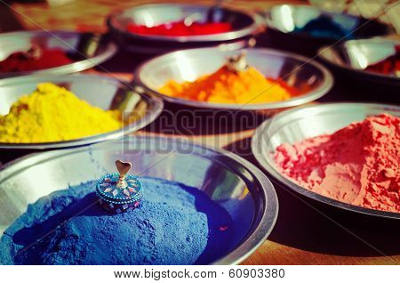 Vintage retro hipster style travel image of India symbol - Colored colorful powder kumkum in bowls on Indian bazaar for Holi and other festivals celebration