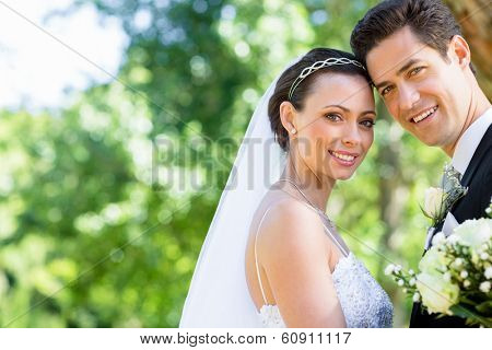 Portrait of happy bride and groom with head to head in garden