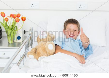Portrait of little boy gesturing thumbs up with teddy bear in hospital bed