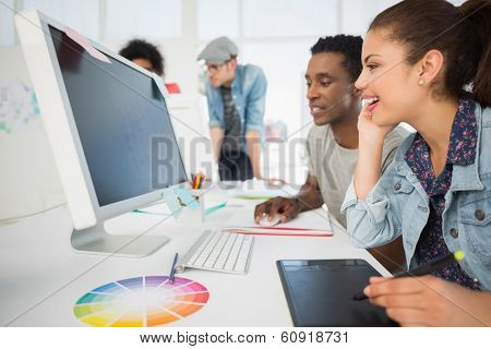 Side view of casual photo editors using graphics tablet in the office