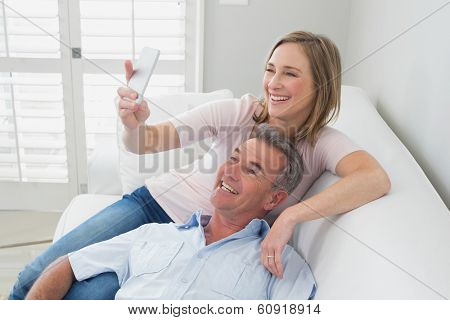 Cheerful loving couple clicking pictures of themselves with mobile phone on sofa at home