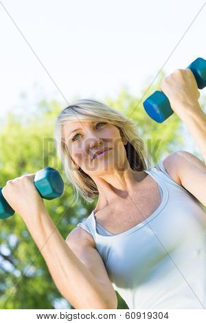 Tilt image of woman lifting dumbbells in the park