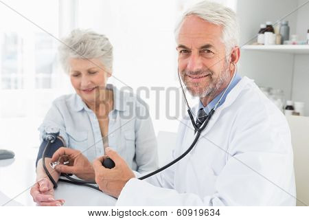 Doctor taking the blood pressure of his retired patient in the medical office