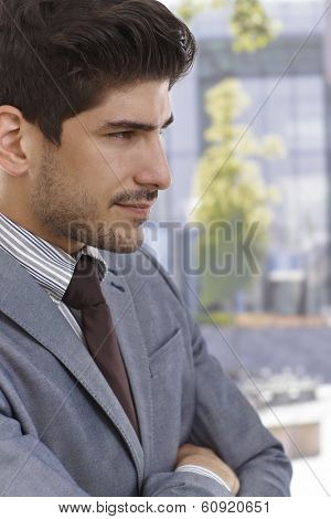 Profile of confident young elegant businessman smiling.