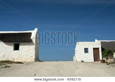 Houses Alongside A Dirt Road