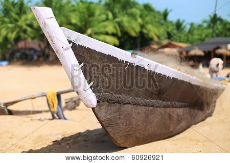 Wooden fishing boat on a sandy beach in sunny day