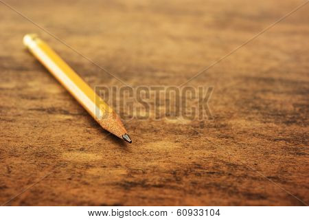 Old yellow pencil on a old used wooden desk. Shallow depth of field.