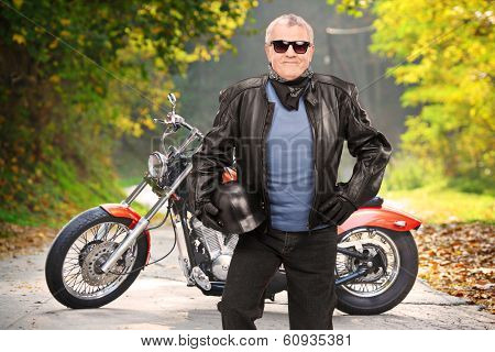 Mature biker in leather jacket standing in front of his chopper on an open road