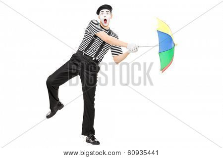Full length portrait of a mime artist holding an umbrella simulating being blown by wind isolated on white background shot with tilt and shift lens