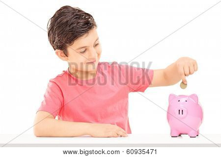 Boy putting money into a piggybank isolated on white background