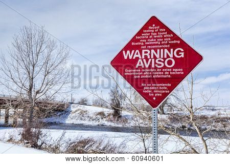 Water pollution warning sign in English and Spanish - South Platte River at Brighton, Colorado, USA.