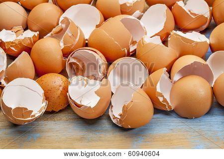 Empty, broken eggshells against wooden background.
