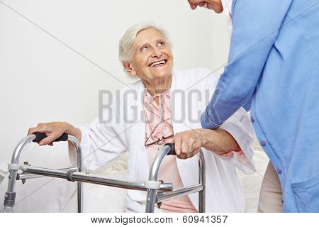 Nurse helping senior citizen patient in nursing home getting up