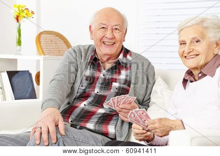Happy senior citizen couple playing cards at home