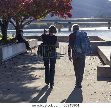 Autumn. Couple Walks Along Embankment Of Burley Griffin Lake Near National Gallery. Canberra. Austra