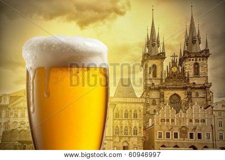 Glass of beer against Tyn Church in Prague