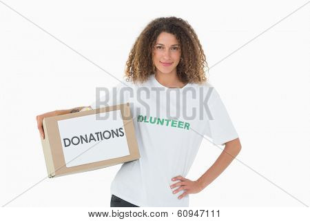Happy volunteer holding a box of donations with hand on hip on white background