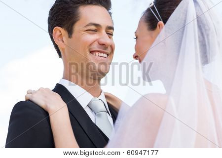 Low angle view of happy newly wed couple against sky