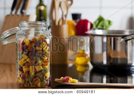 Storage Jar With Colorful Pasta And Cooking Spoon On Worktop
