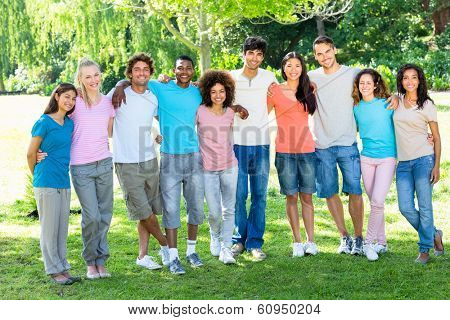 Full length portrait of multiethnic friends standing with arms around in park
