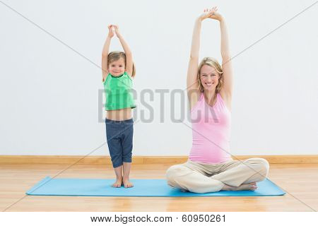 Pregnant mother and daughter doing yoga together in a fitness studio