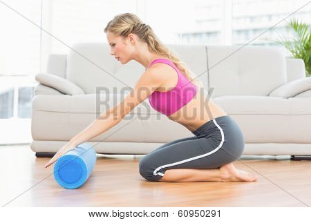 Fit blonde kneeling on floor using foam roller at home in the living room