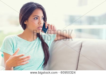 Serious girl sitting on sofa making a phone call at home in the living room