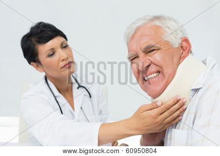 Close-up of a female doctor examining a senior patients neck at medical office