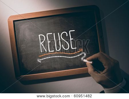 Hand writing the word reuse on black chalkboard