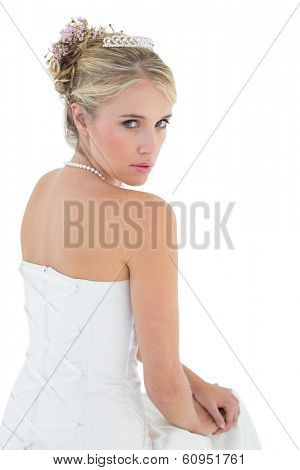 Portrait of sensuous bride sitting against white background