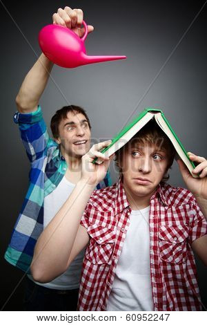 Freaky guy pouring water over his friend hiding under a book, fool�?�¢??s day celebration