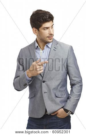 Young businessman driving attention to left by forefinger.