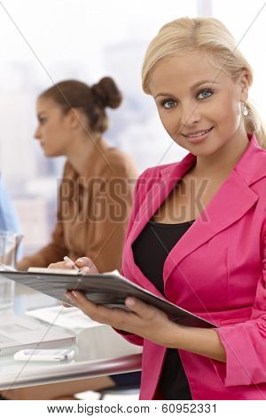 Businesswoman writing notes at businessmeeting, smiling.