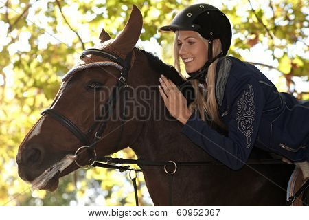 Closeup photo of attractive female rider leaning over horse, smiling happy.